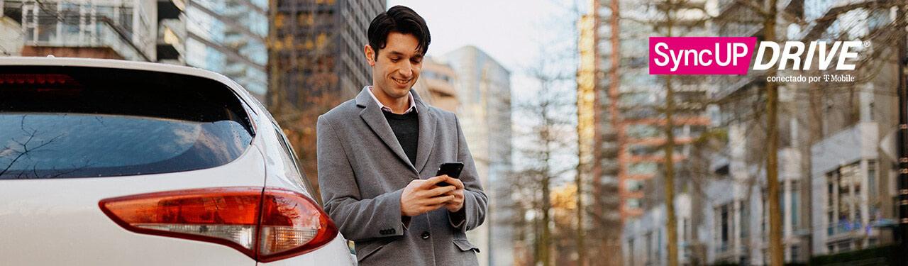 SyncUP DRIVE conectado por T-Mobile. Hombre apoyado sobre su auto mirando su teléfono.